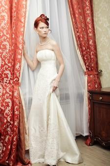 Het gelukkige bruid stellen in hotelruimte