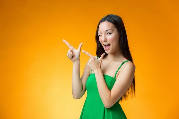 Het gelukkige chinese meisje op gele achtergrond