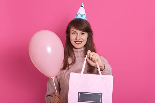 Het gelukkige donkerbruine meisje met roze ballon en bithday in handen aanwezig, houdt mond open, die in verrassing is