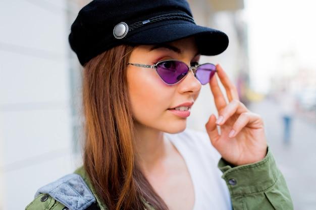 Het gelukkige donkerbruine weoman openlucht stellen. stijlvolle hoed, zonnebril en groene jas.
