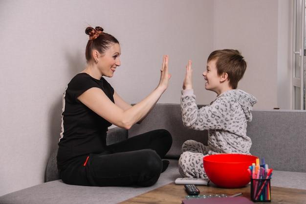 Het gelukkige en grappige mamma met haar zoon slaat handen thuis zittend