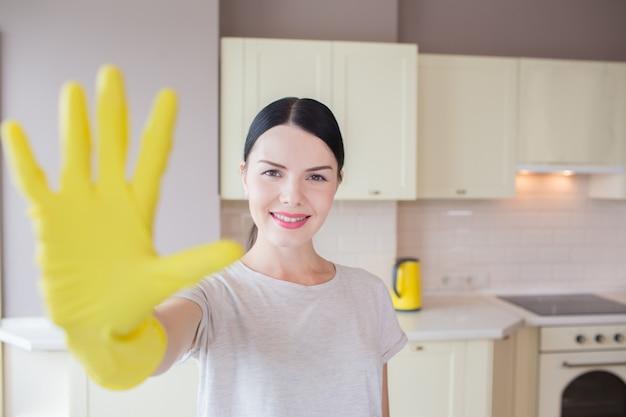 Het gelukkige en positieve brunette bevindt zich in keuken en toont haar indient gele handschoen. ze kijkt op camera en glimlacht. meisje ziet er blij uit.