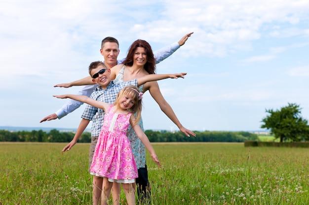 Het gelukkige familie stellen met wapens die in een zonnige weide worden uitgerekt