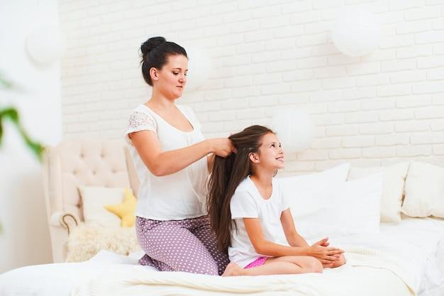 Het gelukkige familie zorgzame mamma vlecht het haar van haar dochter in ochtend na het slapen