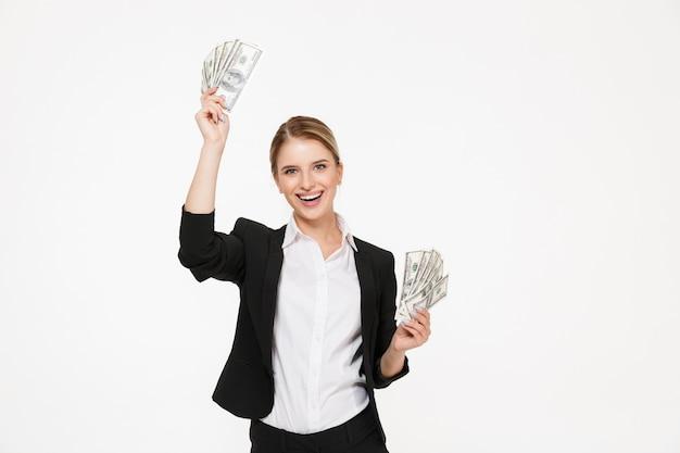 Het gelukkige geld van de blonde bedrijfsvrouwenholding in handen en met open mond over witte muur