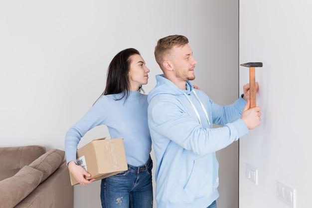 Het gelukkige gezin verhuisde naar een nieuw appartement, de man hangt een foto aan de muur