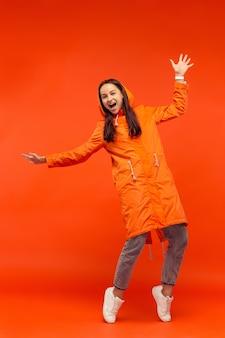 Het gelukkige glimlachende jonge meisje stellen bij studio in de herfst oranje jasje dat op rood wordt geïsoleerd. menselijke positieve emoties. concept van het koude weer. vrouwelijke mode-concepten