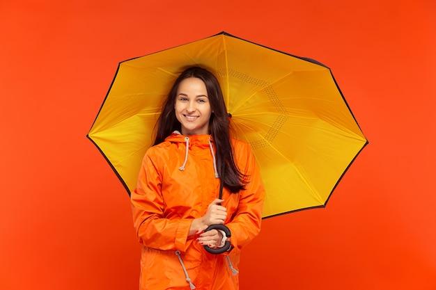 Het gelukkige glimlachende jonge meisje stellen bij studio in de herfst oranje jasje dat op rood wordt geïsoleerd.