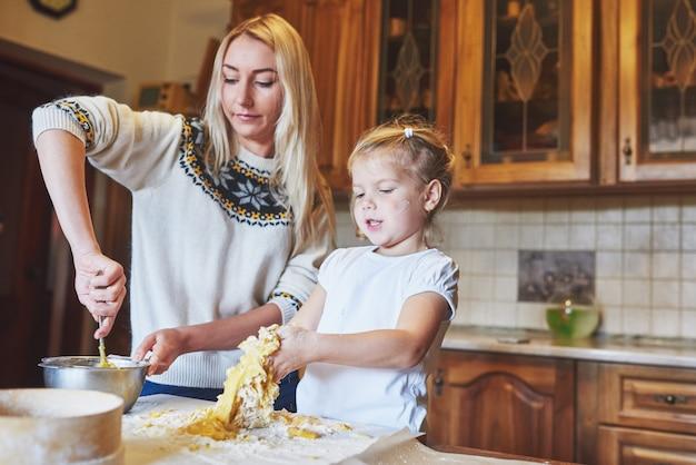 Het gelukkige glimlachende mamma in de keuken bakt koekjes met haar dochter.