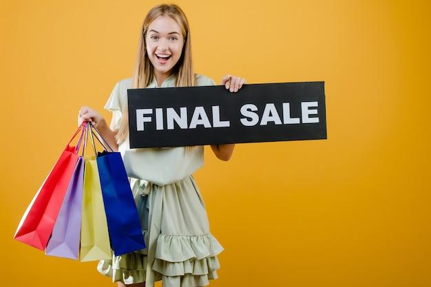 Het gelukkige glimlachende mooie meisje heeft definitief verkoopteken met kleurrijke die het winkelen zakken over geel worden geïsoleerd