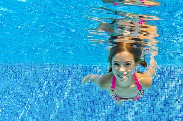 Het gelukkige glimlachende onderwaterkind in zwembad, mooi meisje zwemt en hebbend pret. kids sport op familie zomervakantie. actieve vakantie
