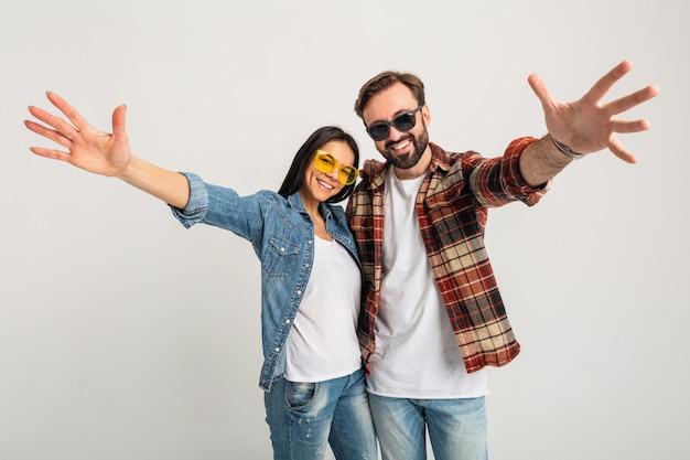 Het gelukkige glimlachende paar dient camera in die op witte studio wordt geïsoleerd