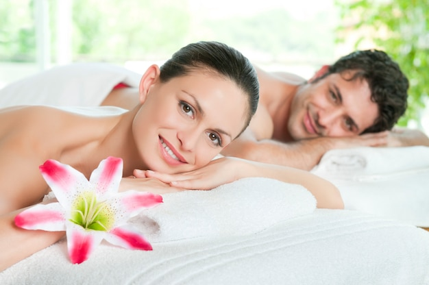 Het gelukkige glimlachende paar geniet van een schoonheidsbehandeling
