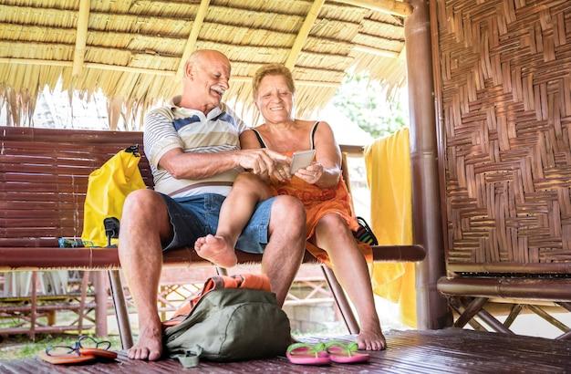 Het gelukkige hogere paar die mobiele slimme telefoon met behulp van ontspant ogenblik in reishotel
