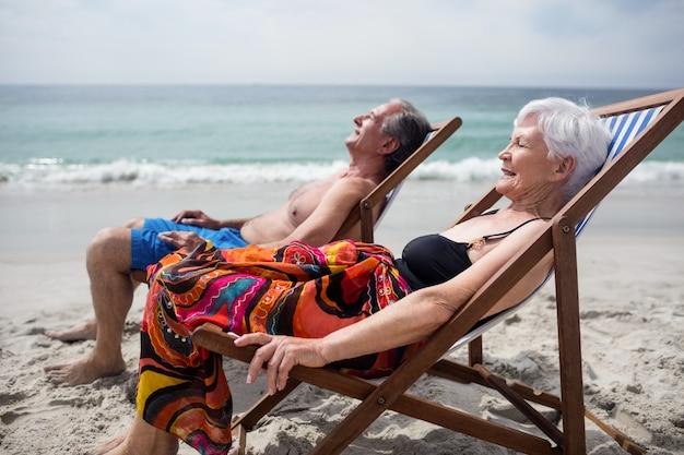 Het gelukkige hogere paar ontspannen op ligstoelen bij strand