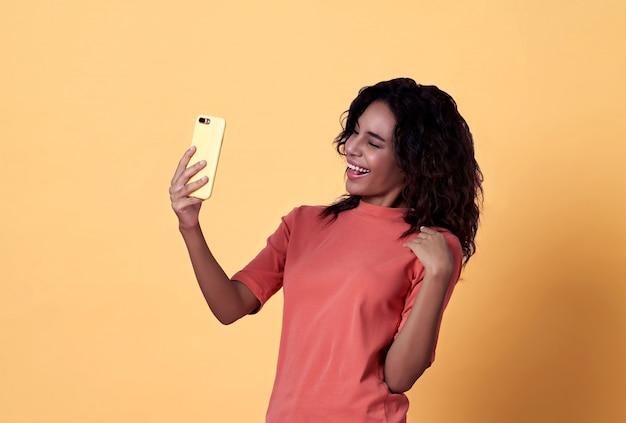 Het gelukkige jonge afrikaanse vrouw selfie vieren met mobiele telefoon over gele achtergrond