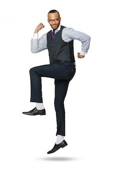 Het gelukkige jonge afrikaanse zakenman hoog springen geïsoleerd op wit.