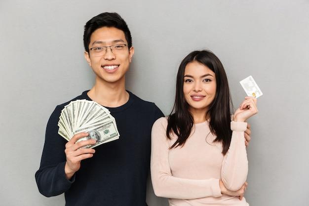 Het gelukkige jonge aziatische houdende van geld en de creditcard van de paarholding.