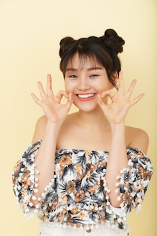 Het gelukkige jonge aziatische vrouw stellen in studio met open glimlach en grappige handgebaren