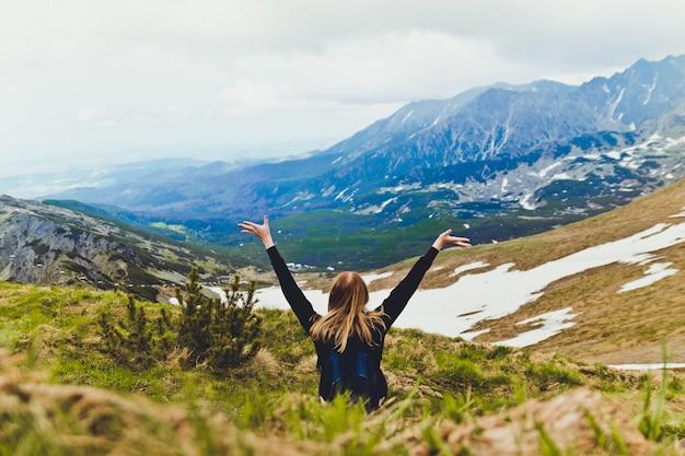 Het gelukkige jonge blonde reist met een blauwe rugzak, zit bovenop een berg en geniet van groen berglandschap