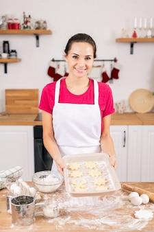Het gelukkige jonge dienblad van de huisvrouwenholding met ruwe kerstkoekjes over keukentafel alvorens hen in de oven te bakken