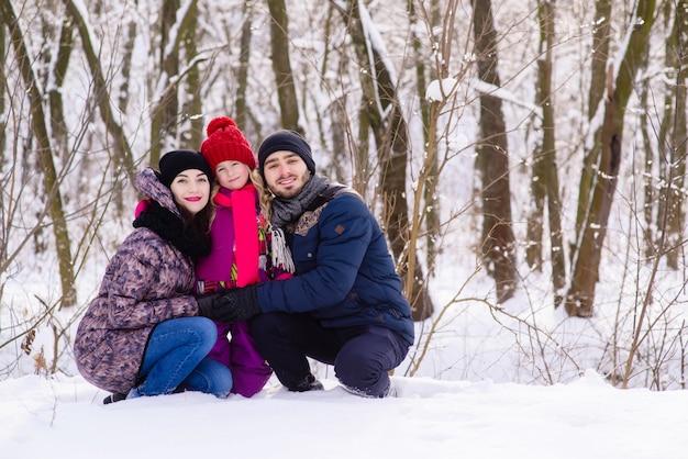 Het gelukkige jonge familie stellen in sneeuwpark