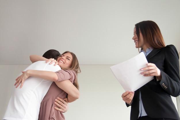Het gelukkige jonge familiepaar omhelzen, kocht net nieuw flatgebouw