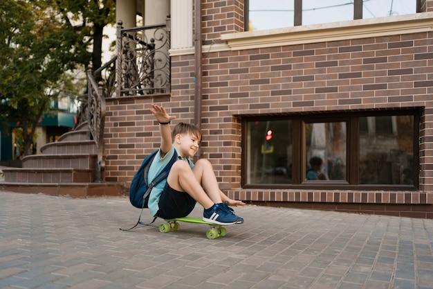 Het gelukkige jonge jongen spelen op skateboard in de stad, kaukasisch jong geitje die stuiverraad berijden