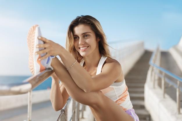 Het gelukkige jonge kaukasische sportvrouw glimlachen