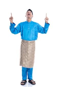 Het gelukkige jonge mannetje dat van maleisië omhoog wijst naar copyspace kijkt