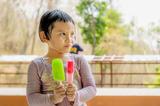 Het gelukkige jonge meisje in een nat overhemd dat ijslolly eet op de natuurlijke buitenachtergrond