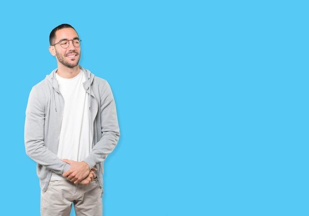 Het gelukkige jonge mens stellen tegen achtergrond
