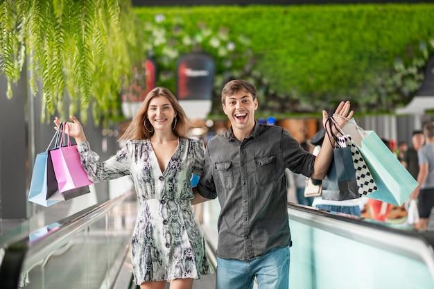 Het gelukkige jonge paar bevindt zich omhelzend op de pakketten van een roltrapholding met grote aankopen in hun handen