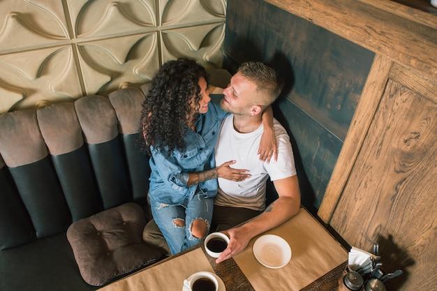 Het gelukkige jonge paar drinkt koffie en glimlacht terwijl het zitten bij het koffie