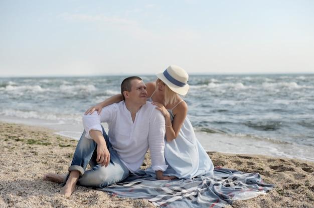 Het gelukkige jonge paar heeft rust dichtbij oceaan en kussen