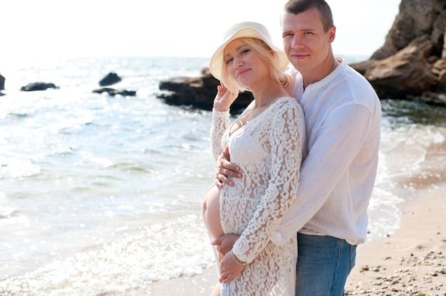 Het gelukkige jonge paar heeft rust en omhelzingen dichtbij oceaan