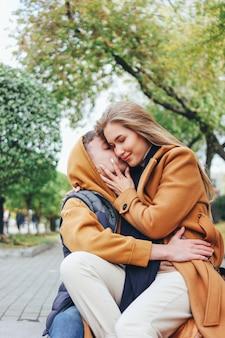 Het gelukkige jonge paar in de vrienden van liefdetieners kleedde zich in het toevallige stijl kussen op de straat van de de herfststad