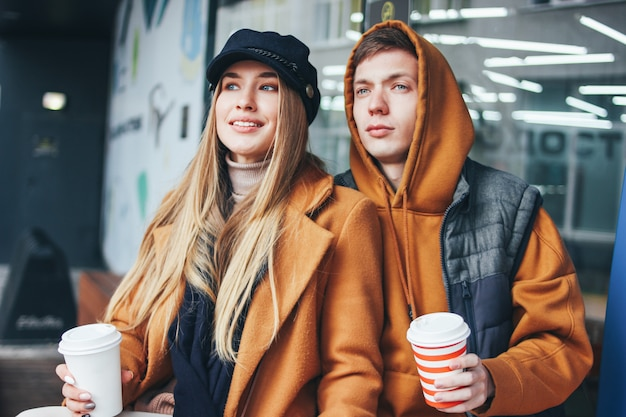 Het gelukkige jonge paar in de vrienden van liefdetieners kleedde zich in toevallige stijl met koffie om samen op de stadsstraat in koud seizoen te gaan lopen