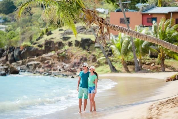 Het gelukkige jonge paar in wittebroodsweken op het strand geniet van romantische vakantie