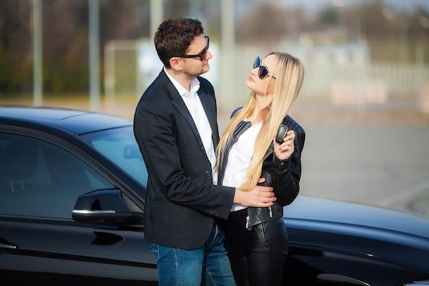 Het gelukkige jonge paar kiest en het kopen van een nieuwe auto voor het gezin