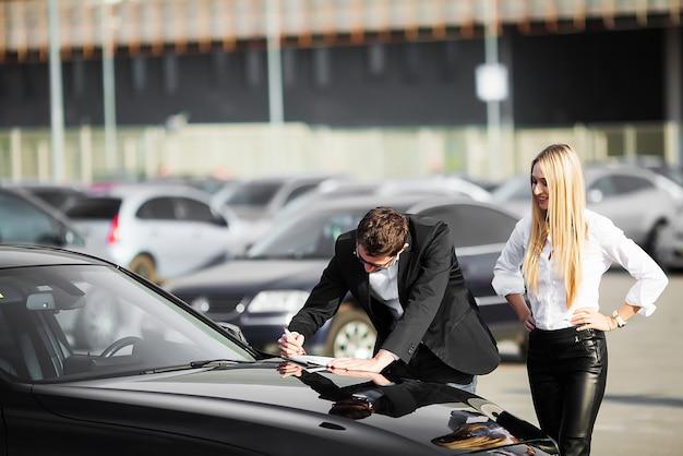 Het gelukkige jonge paar kiest en koopt een nieuwe auto voor het gezin