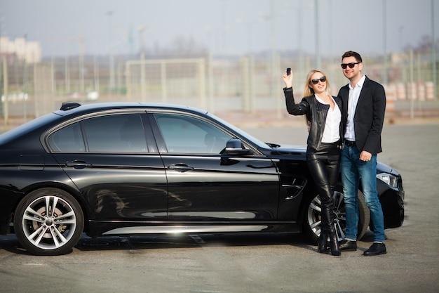 Het gelukkige jonge paar kiest en koopt een nieuwe auto voor het gezin.