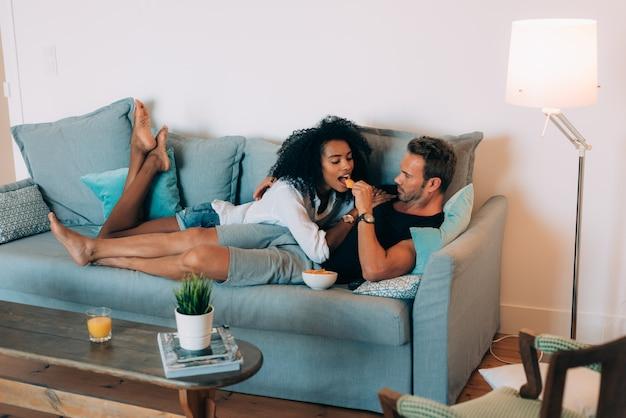 Het gelukkige jonge paar ontspande thuis in de laag die pret het spelen met elkaar hebben