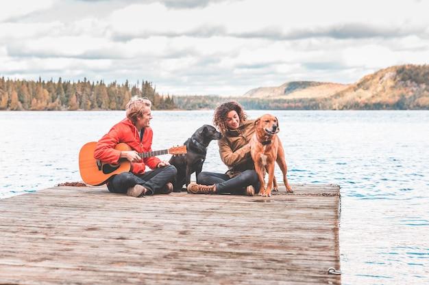 Het gelukkige jonge paar spelen met hond op een dok