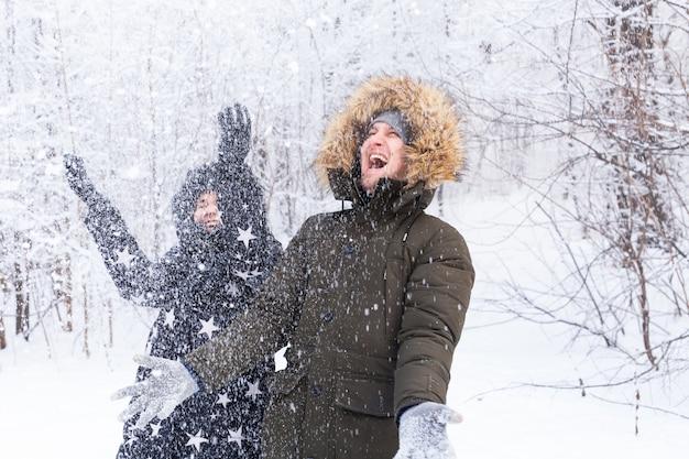 Het gelukkige jonge paar werpt een sneeuw in een de winterbos over