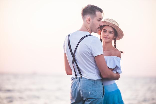 Het gelukkige jonge romantische paar ontspannen op het strand en het letten op de zonsondergang