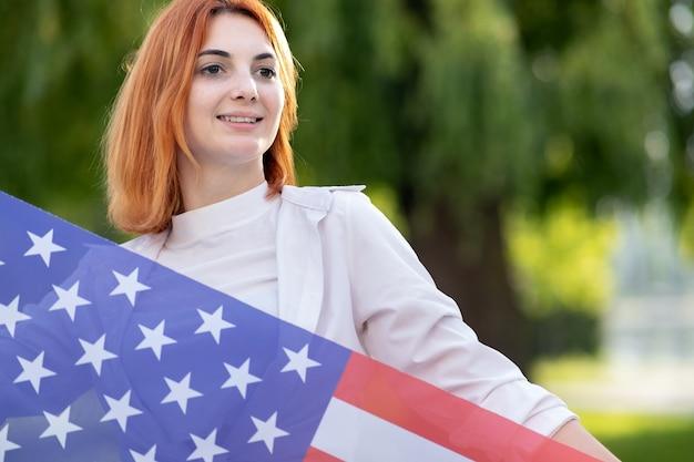 Het gelukkige jonge roodharige vrouw stellen met nationale vlag die van de vs zich buiten in de zomerpark bevinden. positief meisje dat de onafhankelijkheidsdag van de verenigde staten viert. internationale dag van democratie concept.