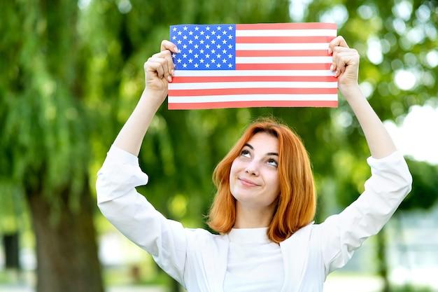 Het gelukkige jonge roodharige vrouw stellen met nationale vlag van de vs omhoog boven haar hoofd buiten in de zomerpark