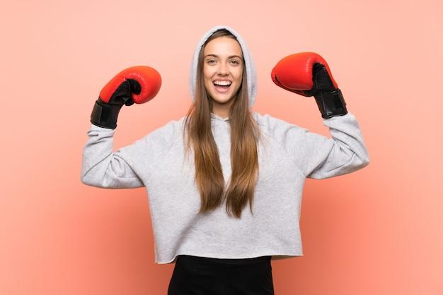 Het gelukkige jonge roze van de sportvrouw met bokshandschoenen