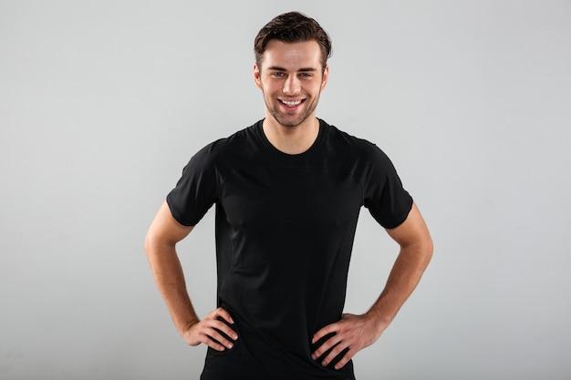 Het gelukkige jonge sportenmens stellen geïsoleerd over grijze muur